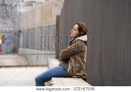 Depressed Young Woman Sitting On Urban City Street Overwhelmed A