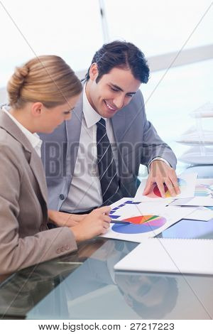Portrait of smiling business people studying statistics in a meeting room