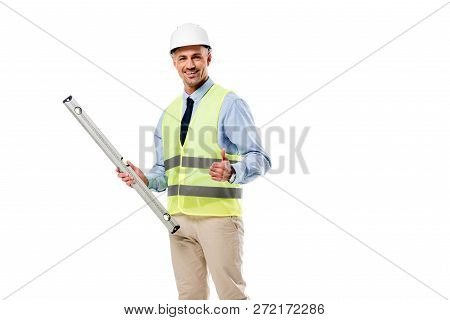 Smilng Engineer Holding Spirit Level And Showing Thumb Up Isolated On White