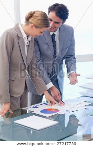 Portrait of smiling business people looking at statistics in a meeting room