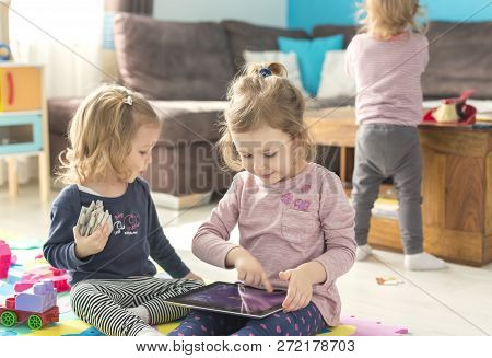 Two Little Sisters Use Tablet At Home And Sit In The Middle Of Toys. Watching Something Funny.