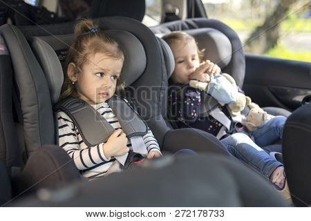 Cute Small Twins In Gray Car Seats In The Car