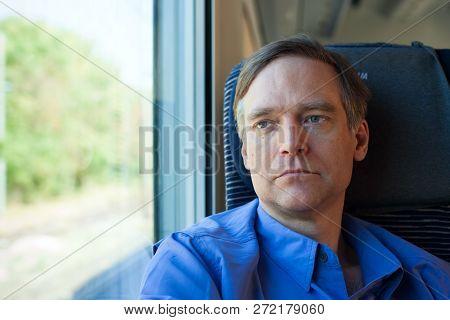 Caucasian Man In Forties Wearing Blue Shirt Sitting On Commuter Train