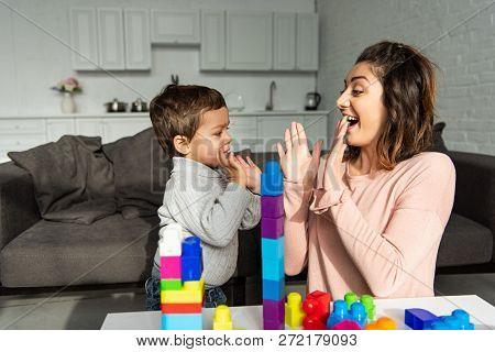 Cheerful Woman Doing Pat-a-cake With Little Son At Home