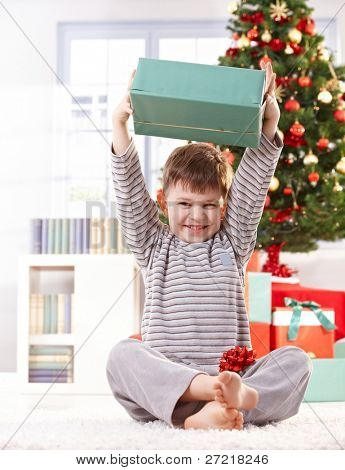 Cute kid sitting in pyjama on floor on christmas morning, raising wrapped christmas gift parcel high, laughing.?