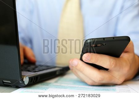 Man In Official Style Clothes Works In Office, Sitting At A Table With Laptop And Smartphone In Hand