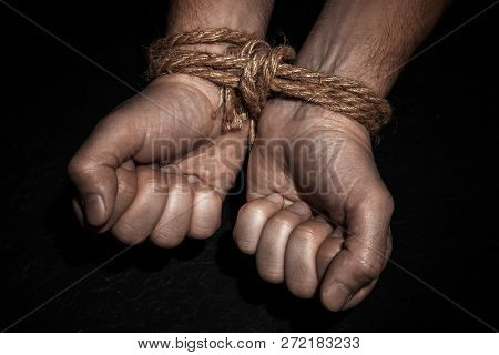 Man With Hands Tied With Rope On Black Background. The Concept Of Slavery Or Prisoner