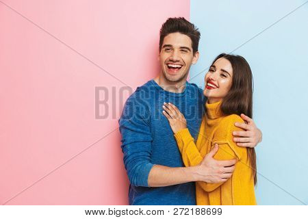 Cheerful young couple standing isolated over two colored background, hugging
