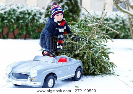 Healthy Little Smiling Kid Boy Driving Toy Car With Christmas Tree. Happy Child In Winter Fashion Cl