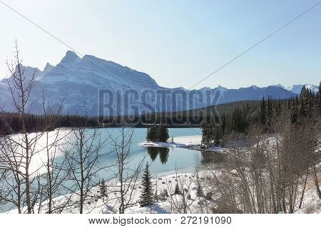 Peaceful View Of Shining Winter Lake, Coast Covered With Snow And Big Mountains On The Background. D