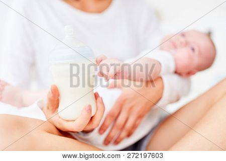 Mother holds baby baby bottle for feeding her baby