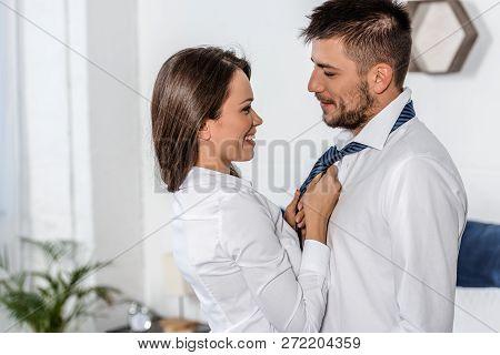 Side View Of Smiling Girlfriend Tying Boyfriend Tie In Morning On Weekday In Bedroom, Social Role Co