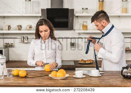Boyfriend Tying Tie And Girlfriend Cutting Oranges In Morning At Kitchen