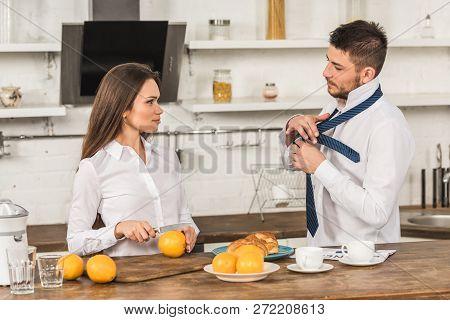 Boyfriend Tying Tie And Girlfriend Cutting Oranges In Morning At Kitchen, Gender Stereotypes Concept