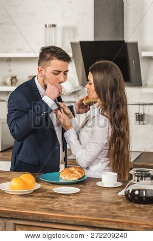 Boyfriend Drinking Coffee And Girlfriend Tying His Tie At Home, Sexism Concept