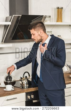 Handsome Man In Suit Pouring Coffee Into Cup And Tying Tie In Morning At Kitchen