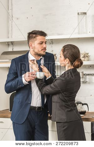 Boyfriend Holding Cup Of Coffee And Girlfriend Tying His Tie At Home, Social Roles Concept