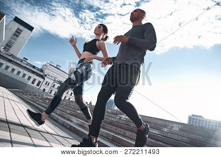 Urban Sports. Full Length Of Young Couple In Sport Clothing Running Through The City Street Together