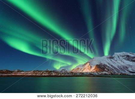 Aurora Borealis Above The Snow Covered Mountain In Lofoten Islands, Norway. Northern Lights In Winte