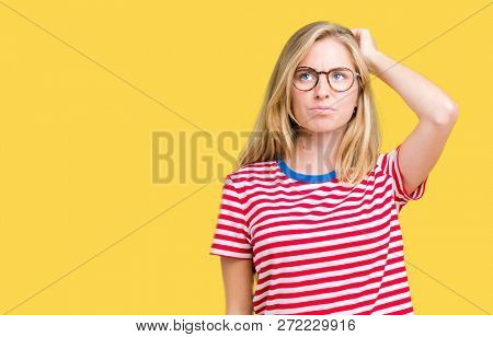 Beautiful young woman wearing glasses over isolated background confuse and wonder about question. Uncertain with doubt, thinking with hand on head. Pensive concept.
