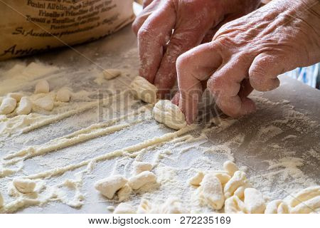Hands Of Italian Woman Making Traditional Fresh Pasta On A Marble Table