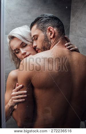 Young Passionate Couple Hugging And Kissing While Taking Shower Together