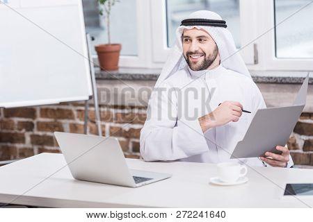 Arabian Businessman Holding Folder And Pen In Office