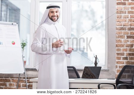 Arabic Businessman Holding Cup With Drink In Modern Office