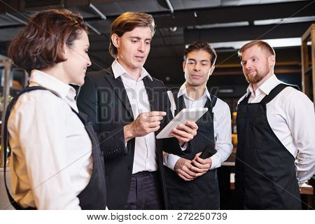 Briefing Of Waiters: Serious Confident Handsome Young Manager Using Tablet And Giving Tasks To Waiti