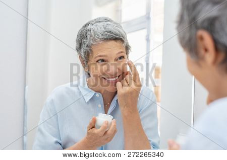 Happy mature woman applying face lotion while looking herself in the bathroom mirror. Senior woman applying anti aging moisturizer on her face. Smiling lady holding little jar of skin cream.
