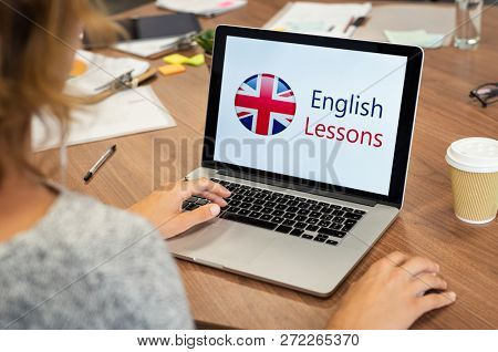 Mature woman learning English online with computer. Laptop screen of woman displaying english lessons poster with British flag. Closeup of student using laptop doing online course on english.