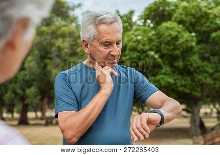 Senior tired man checking pulse after workout. Old man measuring heart rate pulse on his neck and looking sport watch. Aged man times the pulsations at park.