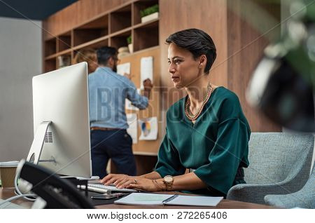 Beautiful businesswoman working on desktop computer in her workstation. Young fashion business woman sitting at desk and using pc with her colleagues in background. Woman sitting on workplace.