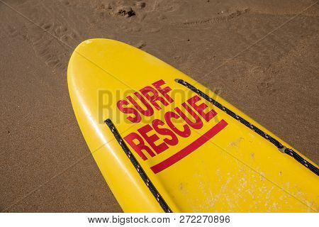 Lifeguard Yellow Board With Surf Rescue On The Wet Sand