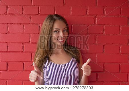 Smiling Pretty Young Woman Showing Thumbs Up. Cheerful Model In Striped Dress Isolated On Red Brick