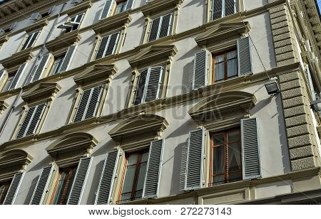 White Facade Of A Nice Building With Many Windows And Light-gray Window Shutters. Historical Archite