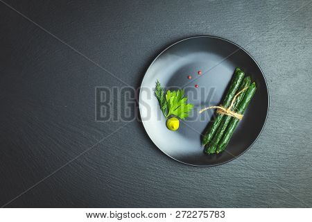 Kabanosy, Sausages Green With Wasabi Made Of Pork In Plate On A Black Stone Surface With Addition Of