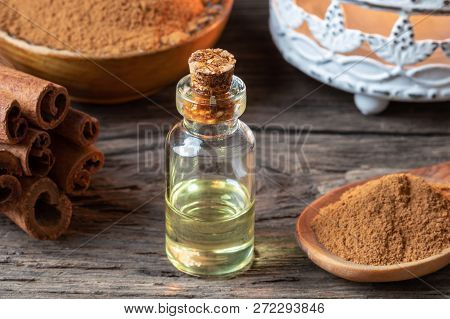 A Bottle Of Essential Oil With Cinnamon Sticks And Powder