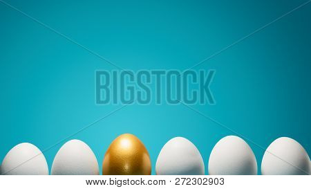 Concept Of Individuality, Exclusivity, Better Choice. One Golden Egg Among White Eggs On Blue Backgr