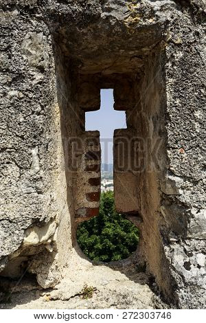 Tomar, Portugal - June 24, 2018:  Fine Example Of An Arrowslit With A Horizontal Slit Creating A Cro