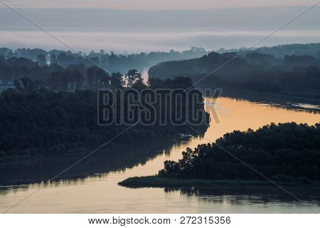 Early blue sky reflected in river water. Riverbank with forest under predawn sky. Cloudy sky on background. Fog hid trees on island. Colorful morning atmospheric landscape of majestic nature. poster