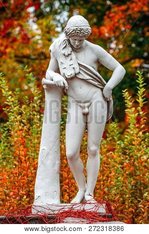 Statue of sensual renaissance era Roman man in lion skin with hunting tube at golden Autumn, Potsdam, Germany poster