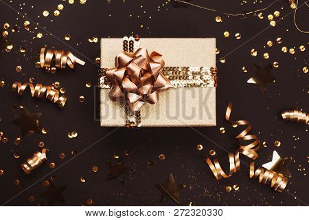 Gift Box With Golden Bow On Black Background With Decoration And Sparkles. Flat Lay. Festive Concept