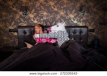 Freaky Man In Unicorn Mask Molest To Scared Girlfriend In Pajama In Bed. Unusual Couple Has Relation