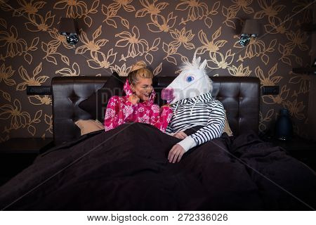 Young Woman In Pajama Sits On Bed And Talks With Funny Boyfriend In Comical Unicorn Mask. Unusual Co