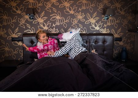 Angry Man In Comical Mask Molest With Scared Young Woman In Pajama On The Bed. Unusual Couple Has Re