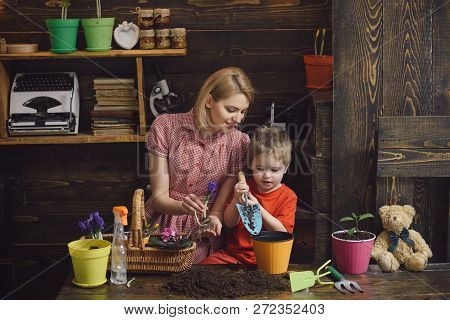 Care Concept. Little Child Help Mother To Care For Plants. Mother And Son Plant Flowers With Care. T