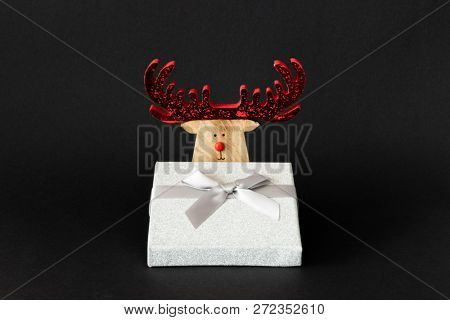 A Christmas decoration reindeer with silver gift box on a black background with space for your content