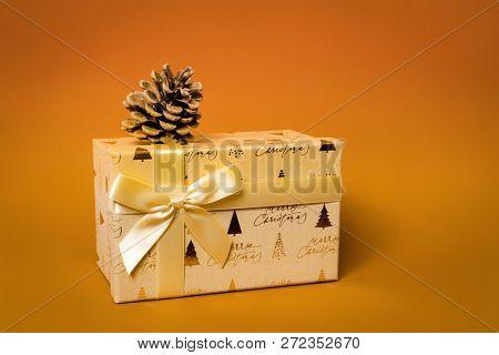 A golden Christmas gift box on orange background