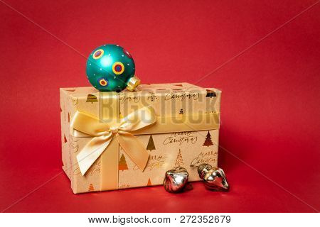 A golden Christmas gift box on red background